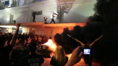Stock Video Footage of Riots - car burning, man throws wood into fire, chaos, yelling