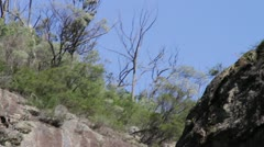 Close up of rock formations while tilting down by raging waterfall, Australia Stock Footage