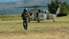 Soldier pilot walking away from helicopter in flight uniform (HD)c  Stock Footage