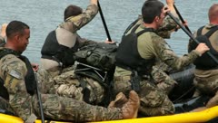 Stock Video Footage of soldiers paddling life boat in survival training (HD)c