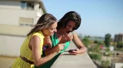 Happy female friends enjoying smartphone on balcony party Stock Footage