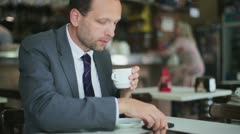 Young businessman with cellphone during coffee break, steadicam shot HD Stock Footage