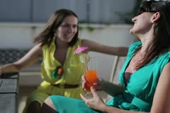 Female friends with exotic drinks on balcony party Stock Footage