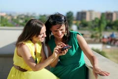 Happy female friends with smartphone high five, outdoor Stock Footage