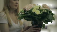 Woman puts on the table a bouquet of flowers Stock Footage