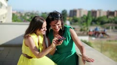 Happy female friends with smartphone high five, outdoor - stock footage
