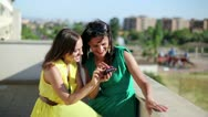 Stock Video Footage of Happy female friends with smartphone high five, outdoor