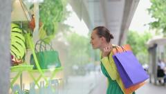 Young shopping woman stopping to marvel shop window, steadicam shot  HD - stock footage