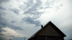 Clouds over the roof of old house at night timelapse Stock Footage