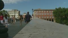 Pedestrians walk over Tiber bridge in Rome (2) pan Stock Footage