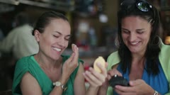 Two happy women correcting make up in cafe, steadycam shot Stock Footage