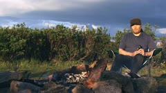 Relaxed Happy Drunk Man Tosses Empty Bottle by Camp Fire Stock Footage