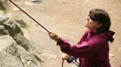 Women belaying a rock climber Stock Footage