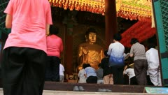 Worshippers bowing down to pray Buddha in temple Stock Footage