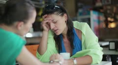 Female friend comforting sad woman in the restaurant, steadycam - stock footage