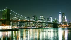 view of Manhattan skyline and Brooklyn bridge at night. Time lapse and loopable - stock footage