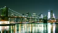 Stock Video Footage of view of Manhattan skyline and Brooklyn bridge at night. Time lapse and loopable