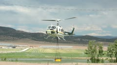 Helicopter loading buck with water to fight fire P HD 0499 Stock Footage