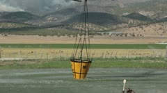 Helicopter water bucket flies to forest fire P HD 0526 - stock footage