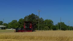 Driving by a farm grain field with combine in the field Stock Footage