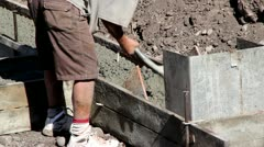 Man Shoveling Cement in Footings for House - stock footage