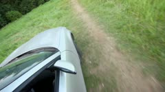 Car ride by grass field, closeup sideview from above Stock Footage