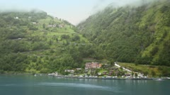 Buses ride by mountain road among forest to coastal village Stock Footage