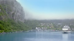Fiord with huge liner near coastal village under mountain - stock footage