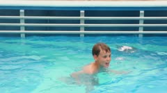 Boy swims in pool from which vapor rises up Stock Footage