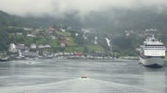 Rescue boat float on fiord to village and huge liner near shore - stock footage