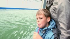 Son speaks with his mother when watch on huge cruiser Stock Footage