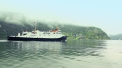 Passengers ship float in fiord at background of coastal village - stock footage
