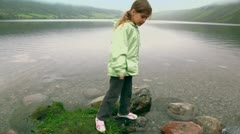 Little girl checks stone in water of fiord with mountains - stock footage