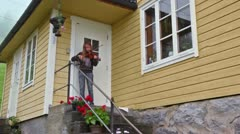 Little girl plays on violin for tourist at porch of house Stock Footage