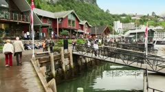 Many tourists walk on quay of coastal village at spring day Stock Footage