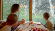 Woman with her kids sit at table and eat in front of window Stock Footage