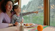 Mother and daughter sit at table with food and watch mountain Stock Footage