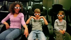 Two kids with their mother in 3d stereo glasses sit at cinema Stock Footage
