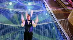 Bartender juggles by four bottles at background of pool with net Stock Footage