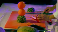 Cook cuts orange slices for fruit statuette on competition Stock Footage