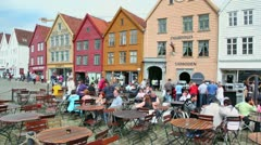 People walk by street and sit in cafe, panorama at summer day Stock Footage