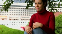 Woman sit and smile under leaves at background of huge liner Stock Footage