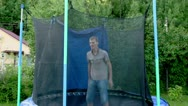 Man jumps on trampoline at background of country house Stock Footage