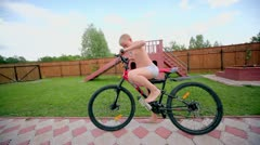 Boy in underpants ride on bike by road at homestead Stock Footage
