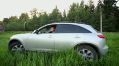 Man on crossover ride around by grass, at background of village Stock Footage