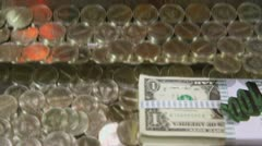 Stock Video Footage of Bundle of banknotes of american dollars and coins on moving tray