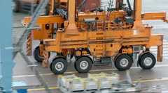 Machine with several wheels rides by asphalt at industrial zone Stock Footage
