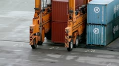 Machine with several wheels rides among containers at port Stock Footage