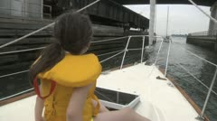 Little Girl on Front of Sailboat going by Bridge Stock Footage