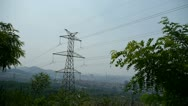 Stock Video Footage of High-voltage wire tower in urban city,wind tree,distant mountain & hill.
